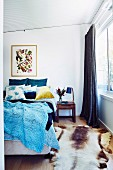Blue knitted bedspread on double bed and animal fur rug in bedroom