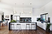 Elegant open kitchen with island, bar stools, dining area with classic chairs in the background