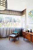Upholstered armchair and fifties style sideboard in front of window with airy curtain