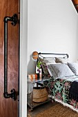 Glance into the guest room on bed with metal frame and rollable bedside table