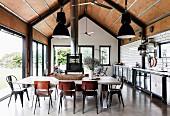 Offene Küche im Industriestil, mit Betonboden, U-Bahn-Fliesen und holzverkleideter Decke, im Vordergrund langer Esstisch mit Stühlen