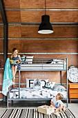 Etagenbett mit Metallgestell und Geschwister im Kinderzimmer mit Holzverkleidung
