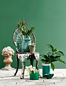Vintage metal chair surrounded by plants and sculpture against green wall