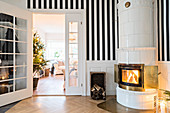 Fire lit in round tiled stove against striped wall