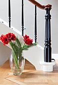 Bouquet of red amaryllis in glass vase next to staircase balustrade