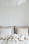 Bed linen in pale shades against board wall