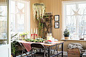 Rustic metal dining table and folding chairs in front of yellow board walls