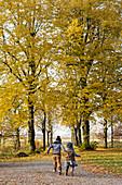Zwei Kinder laufen Hand in Hand durch den Herbstwald