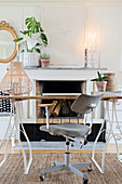Grey office chair and desk in front of open fireplace with ornaments