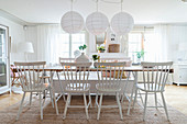 Windsorstühle und Bank am langen Tisch im weißen Esszimmer