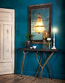 Deep blue hallway with console table on branches as legs and chandelier reflected in mirror