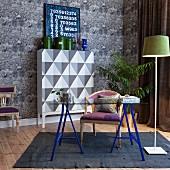 Glasplatte auf blauen Böcken, Stehlampe und Armlehnstuhl vor Highboard mit grafischem Muster