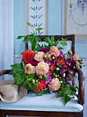 Opulent bouquet with dahlias and raspberry branches on chair