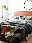 Masculine bedroom with leather headboard, blue checked sheets, green throw and round, leather mirror