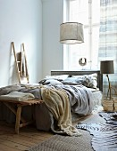 Sand-coloured textiles and driftwood accessories in bedroom