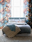 Pastel bed linen and blankets on double bed in front of curtains with pattern of angels