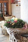 Advent wreath with four colourful candles on sheepskin rug on bench next to fireplace