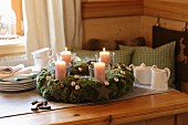 Moss Advent wreath with Christmas baubles and candles in glass jars