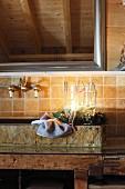 Adventskranz mit Schwimmkerzen in hohem Glasgefäss, verziert mit Kiefernnadeln