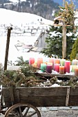 Colourful pillar candles on weathered wooden board outdoors