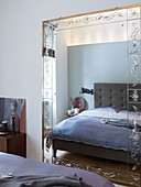 Grey-upholstered bed reflected in mirror with etched ornamental frame
