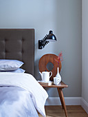 Old wooden chair used as bedside table next to bed with button-tufted headboard