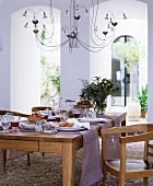 Purple runners on set oak table below halogen chandelier in Mediterranean loggia