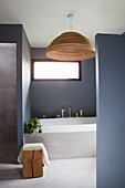 Bathtub and window in bathroom with grey walls