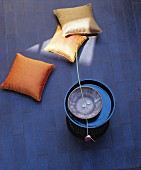 Elegant cushions, side table and allium flower lying across bowl on leather rug