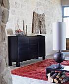 Rustikaler Wohnbereich mit schwarzem Sideboard, Tischleuchte mit Holz-Lampenfuss und rotem Flokatiteppich