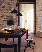Set, black dining table and stools in front of open doorway in stone wall