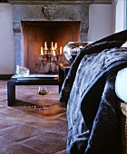 Romantic atmosphere with candelabra in open fireplace, glass of wine and fur blanket in front of black coffee tables
