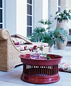Elegant rattan couch with floral cushions next to claret tray table