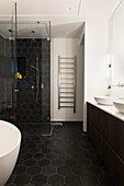 Black honeycomb tiles in bathroom with glass shower cabinet and heated towel rail
