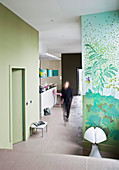 Woman walking through open-plan interior with green walls
