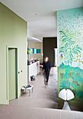 Frau geht durch offenen Wohnraum mit grünen Wänden