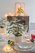 Christmas table decorated with artificial snow, small fir trees, white crockery and lit tealights