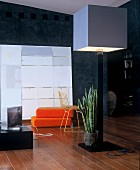 Standard lamp with cubist lampshade in front of orange floor cushions and modern artwork