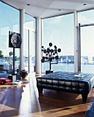 Black leather ottoman in front of modern objets d'art and glass walls with view of lake