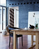 Simple wooden table, glass vase and black chair
