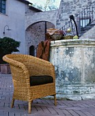 Wicker chair with seat cushion in front of vintage fountain in Mediterranean courtyard