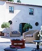 Möblierter, mediterrane Innenhof mit Rattan-Sitzgelegenheiten und rotem Couchtisch