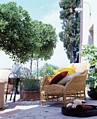 Wicker armchair with various cushions on traditional Mediterranean stone terrace