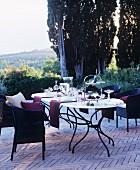 Gedeckter Tisch und Rattansessel auf mediterraner Terrasse