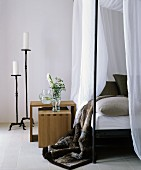 White candles in large black candlesticks next to bed with canopy and fur blanket