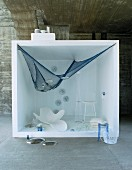 White furniture and blue fishing net hung up in white cube in front of concrete wall