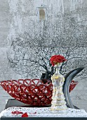 Rose in glass woman-shaped vase in front of red glass dish and black sea fan coral