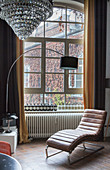 Leather couch and arc lamp in front of old lattice window