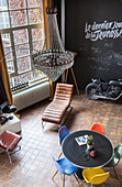 View down into industrial loft apartment with chalkboard wall and designe furniture