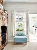 Blue ottoman with cloud-shaped cushion below lattice window